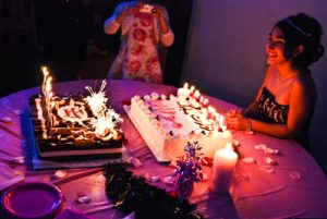 lit sweet sixteen cakes in front of birthday girl