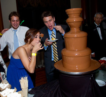 girl tasting chocolate fountain at chocolate theme party
