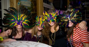 girls with mardis gras masks on yellow purple green theme party