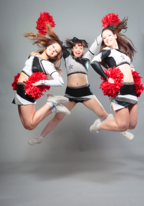 cheerleaders jumping with red pom poms