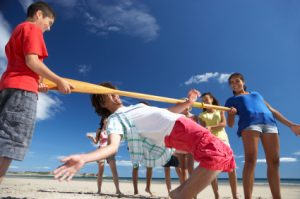 teenagers doing limbo on the beach at luau theme party