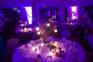 fairy tale centerpiece lighting hanging votices on branches with purple uplighting